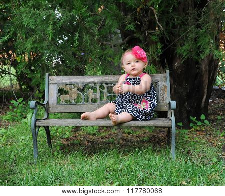 Little girl sits on wooden park bench. She is wearing a summer frock in black and white. Her hair has a pink flower hair bow. Her thoughts are quiet and peaceful.