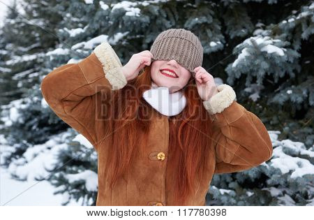 Winter woman outdoor portrait with cap covering eyes, snowy fir trees background