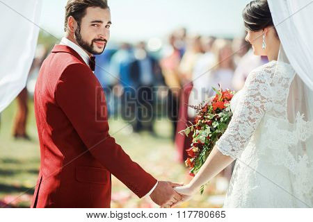 Groom pointedly looking at camera while standing in wedding ceremony arch with bride's hand on backg