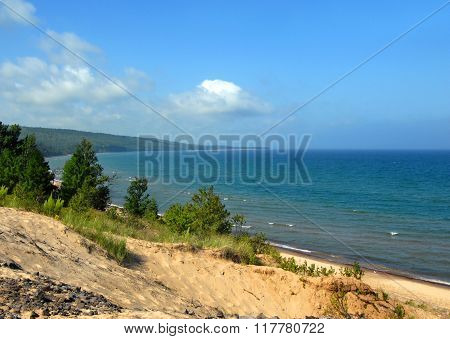 Curving shoreline disappears into the distance on Lake Superior in the Upper Peninsula of Michigan. Blue sky blue water and sandy dune complete landscape.