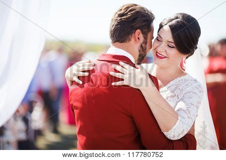 Bride and groom dancing at wedding ceremony on background of arch. Marsala color decoration style.