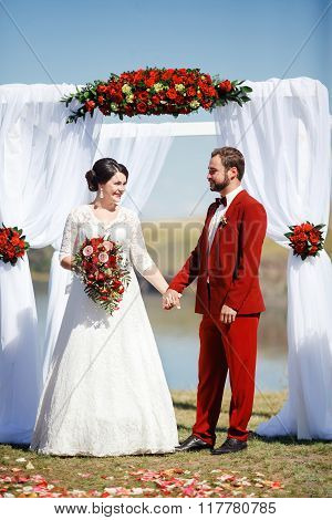 Bride and groom during wedding ceremon, arch flowers outdoors.