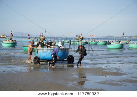 Fishermen pull round plastic boat from the sea. The fishing harbor of Mui Ne, Vietnam
