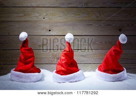 Three Santa Hats In Snow