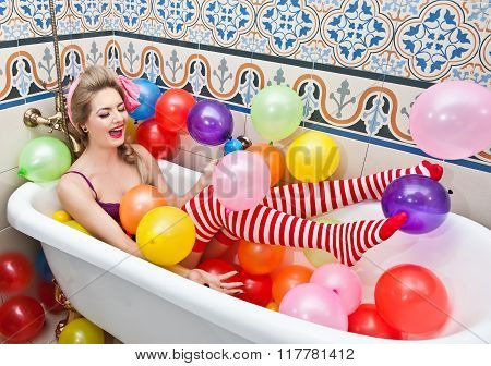 Blonde woman with sunglasses playing in her bath tube with bright colored balloons. Sensual girl
