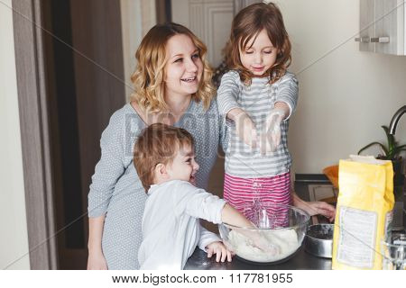 Mom with her children cooking holiday pie in the kitchen together, casual still life photo series