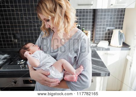 Young mother is holding her newborn baby