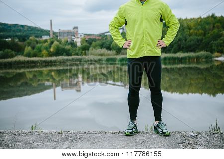 Runner at the lake resting against green trees
