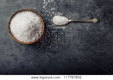 Salt. Coarse grained sea salt on granite - concrete  stone background with vintage spoon and wooden
