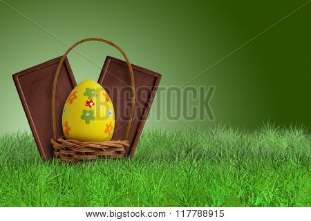 Easter chocolate bars and basket on green background