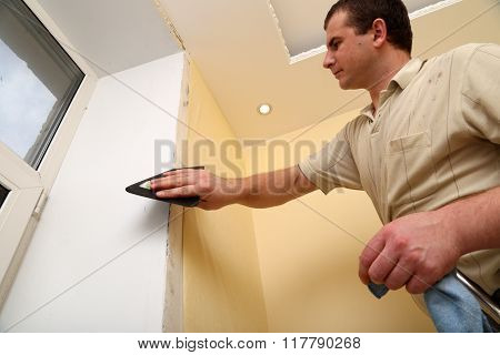 Man Worker repairing the house and putting up wallpaper