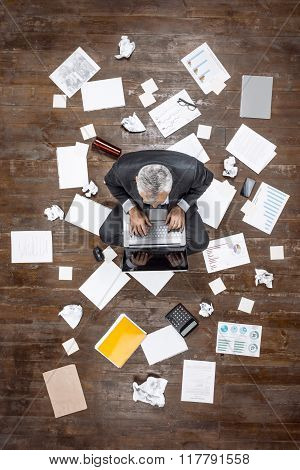 Top view creative photo of senior businessman on vintage brown wooden floor. Businessman sitting on office objects and working with laptop. There are documents on floor