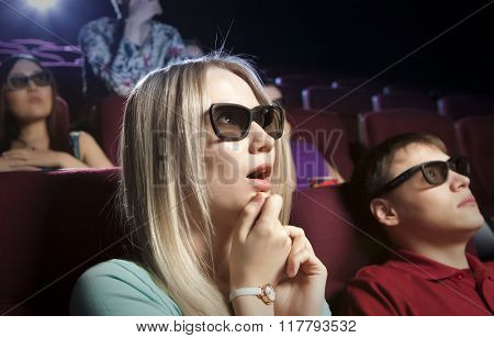 Young blonde women sitting at the cinema, watching a film. Cinema photo series