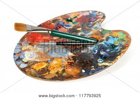 Artist palette with paintbrushes isolated over white background