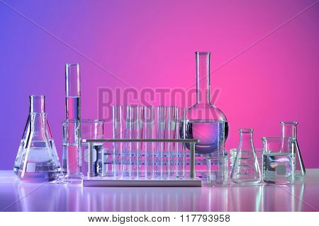 Laboratory glassware with liquid over reflective table
