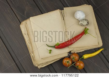 Recipe book and vegetables. Chili pepper and tomatoes. Place for your text.