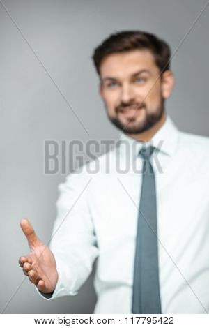 Close up photo of young attractive businessman. Businessman smiling and proposing to shake hand