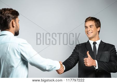 Studio shot of young attractive businessmen. Businessmen smiling, showing thumb up and shaking hands
