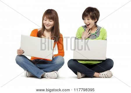 Two friends using laptop computers
