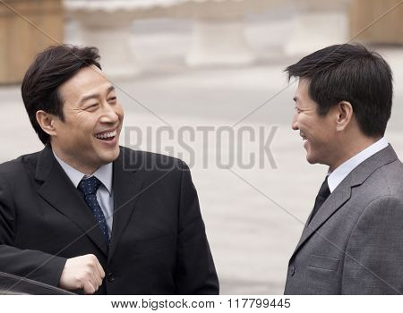 businessmen smiling to each other
