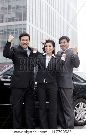 Three businesspeople outdoors cheering