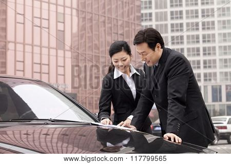 Businesspeople working outdoors on car