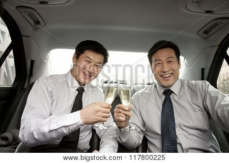 Businessmen toasting in back of car