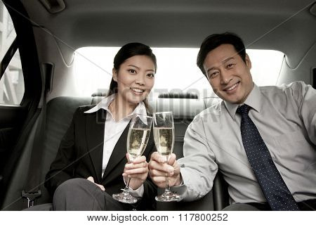 business people toasting champagne back of car