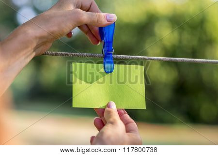 Female Hand Hanging A Blank Green Card With Plastic Peg