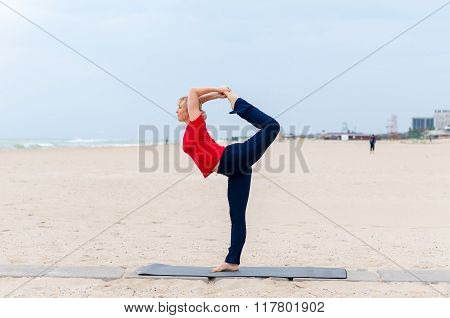 Sporty fit blond woman in red and dark blue sportswear working out outdoors on summer day, doing Nat