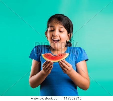 indian child girl eating watermelon isolated on green background, asian girl with a portion of the w