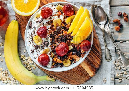 Yogurt with baked granola and berries in small bowl, strawberries, blueberries. Granola baked with n