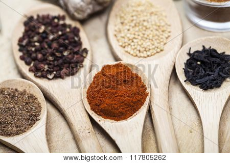 Various colorful spices on kitchen spoons over grunge wooden table background