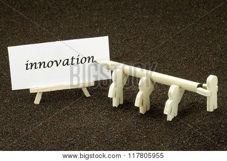 Small wooden males writing the word innovation