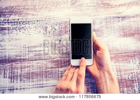 a mobile telephone in hands for a girl is isolated on a wooden background