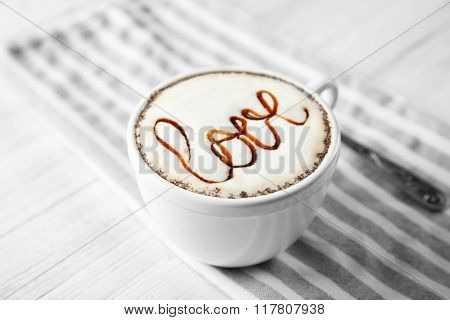 Cup of cappuccino with chocolate syrup on light wooden table
