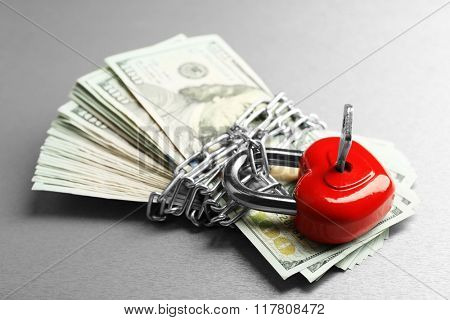 Dollars currency with lock and chain on gray  background
