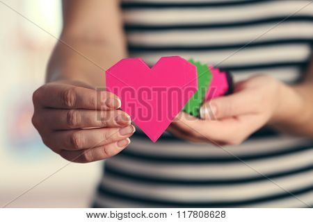 Closeup of plastic puzzle hearts in female hands