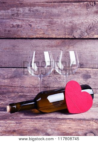 Red heart with wine bottle and glasses on wooden background