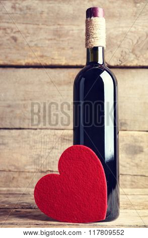 Red felt heart with wine bottle on wooden background