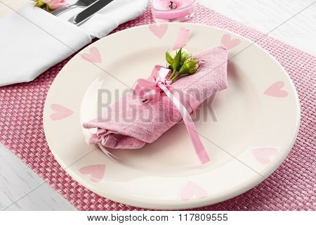 Table setting with plates, cutlery, napkin and candles on pink background