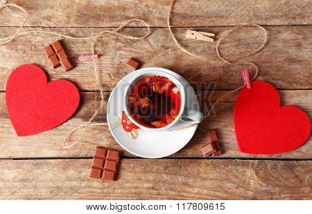 Cup of tea with two red hearts and piece of chocolate on wooden background closeup