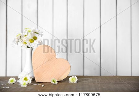 Wooden heart with flowers on a white wall background