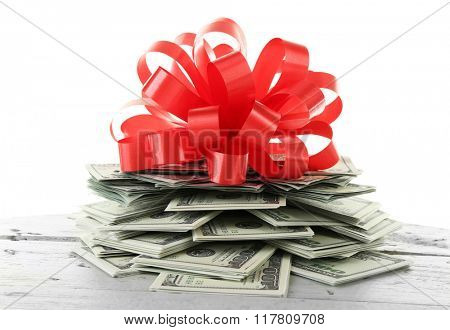 Pile of dollars with bow as gift isolated on white