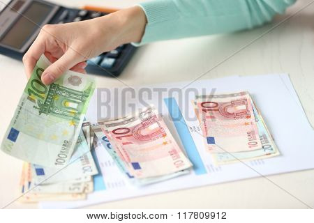 Woman counting money at the table