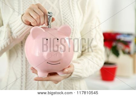 Woman holding piggy bank with inserted dollar banknote. Savings money concept