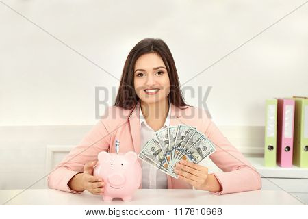 Happy young woman holding piggy bank with dollar banknotes. Money savings concept