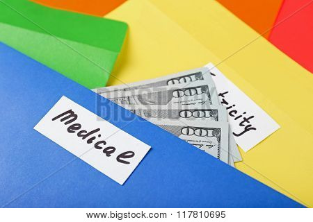 Distribution of money, financial planning, dollars in bright envelopes, closeup