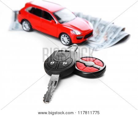 New red car with keys and dollar banknotes on white background