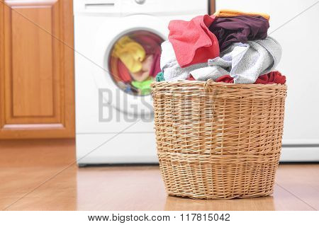 Basket with laundry and washing machine.